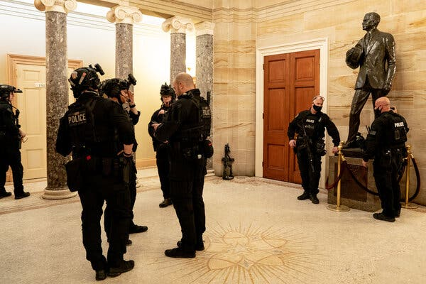 Police officers huddled in the Capitol on Jan. 6 after the building had finally been marked clear following the violent assault from a pro-Trump mob.