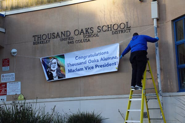 A janitor hung a banner on the Thousand Oaks Elementary school that featured a drawing of Vice President Kamala Harris in Berkeley, Calif., on Wednesday.