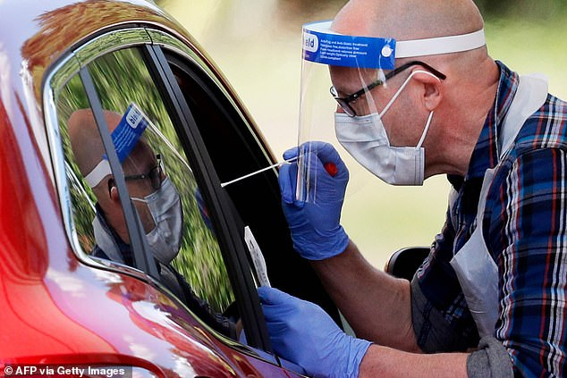 A Covid tester leans into a car to take a swab at Chessington World of Adventures, near London