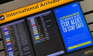 A public health campaign message is displayed on an arrivals information board at Heathrow airport.