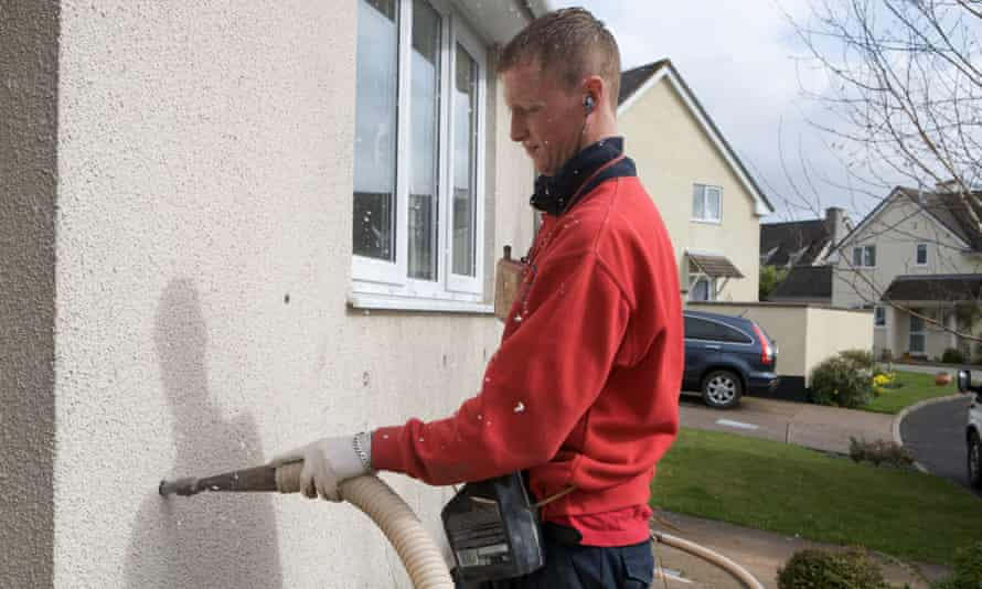 A man fills a cavity wall with insulation.