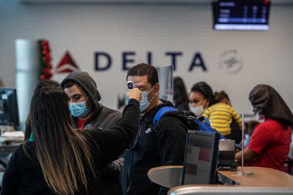 A passenger receives a temperature check at LaGuardia Airport in New York.Eastern Iowa Airport will screen all outgoing passengers for the coronavirus.