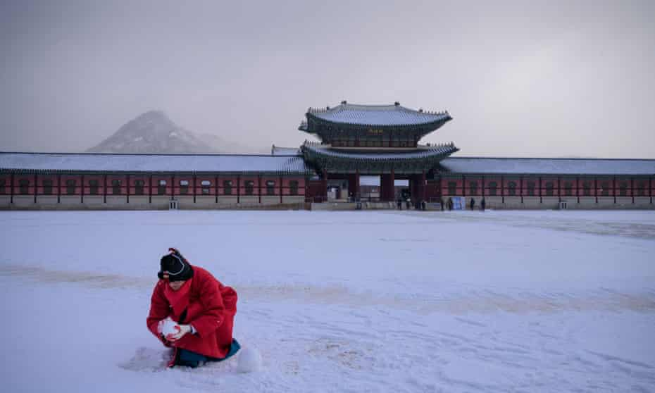 A tour guide makes snowballs in a courtyard of Gyeongbokgung palace, Seoul, South Korea in 2020.