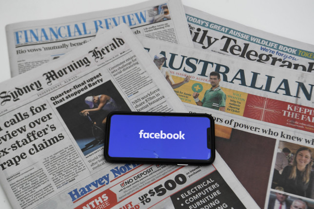 epa09020239 An illustration image shows a phone screen with the Facebook logo and Australian Newspapers at Parliament House in Canberra, Australia, 18 February 2021. Social media giant Facebook has moved to prohibit publishers and people in Australia from sharing or viewing Australian and international news content in response to Australia's proposed media bargaining laws. EPA/LUKAS COCH AUSTRALIA AND NEW ZEALAND OUT