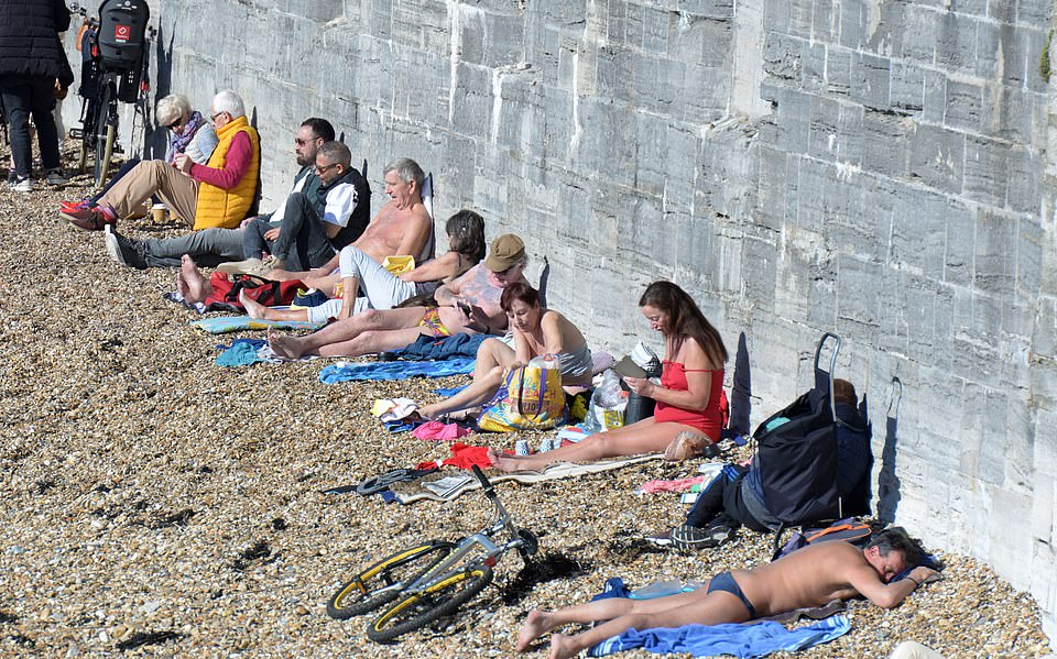 People are pictured sitting on the shingle beach at the Hot Walls in Portsmouth, Hampshire today as they enjoyed the sunshine despite lockdown rules dictating that people should only go out for exercise or shopping