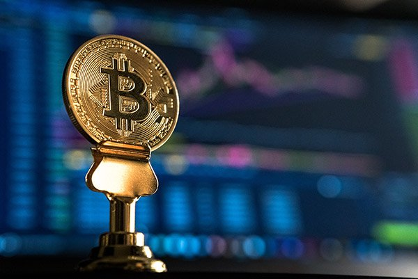 This photoBitcoin on stand in front of trading chart