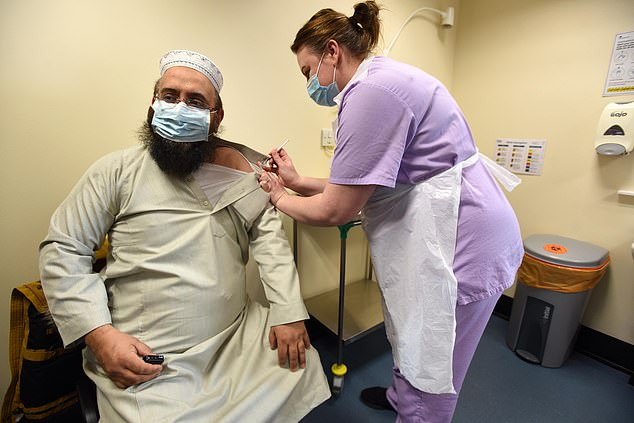 Above is Mufti Zubair Butt, a muslim imam and chaplain, receiving his first dose of the Covid-19 vaccine at Whetley Medical Centre in Bradford