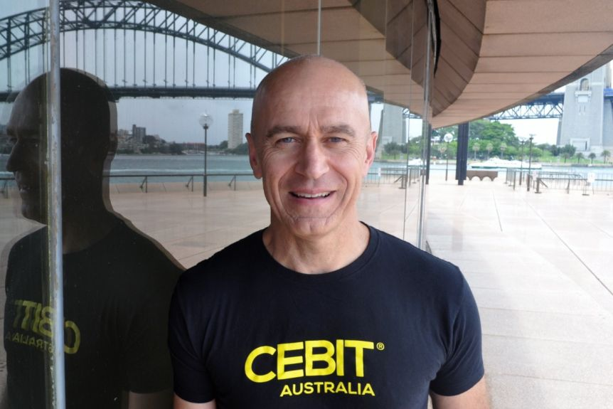 Stephen Scheeler, wearing a black t-shirt in front of a glass wall, reflecting the Sydney Harbour Bridge.