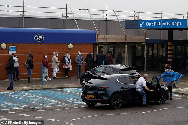 Pictured:People queue outside the Outpatients Department at the Basildon and Thurrock hospital in south west Essex, eastern England, on January 1, 2021