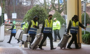 """Workers carry luggage of passengers to the Holiday Inn Hotel near Heathrow Airport, as Britain introduces hotel quarantine programme for arrivals from a """"red list"""" of 30 countries."""