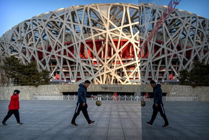 Pedestrians pass the National Stadium in Beijing, which host some events of next years Winter Olympics. China intends to run trials of its digital currency this year and have it ready for use during the games