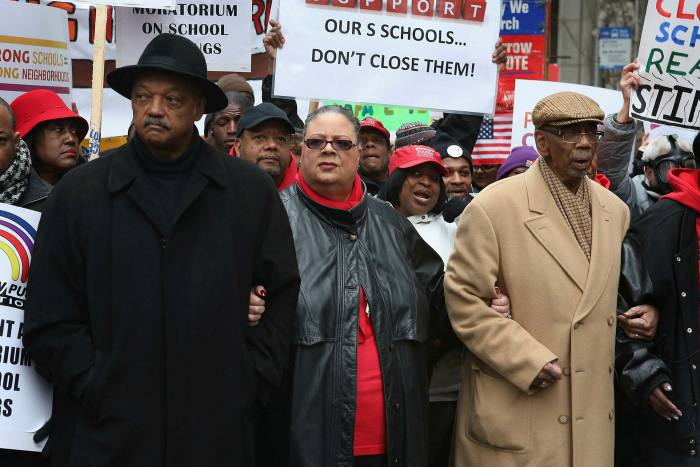 Flanked by Reverend Jesse Jackson, left, and Congressman Bobby Rush to protest school closures in 2013