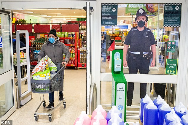 A shopper wearing a face mask is seen passing a cutout of a police officer in the window of a Morrisons store in south London in January this year