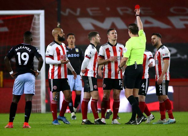 Sheffield United's Phil Jagielka (centre) sees his yellow card upgraded to a red card