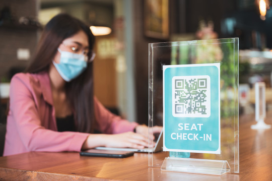 QR code scan for check in before entering coffee shop social distancing rule