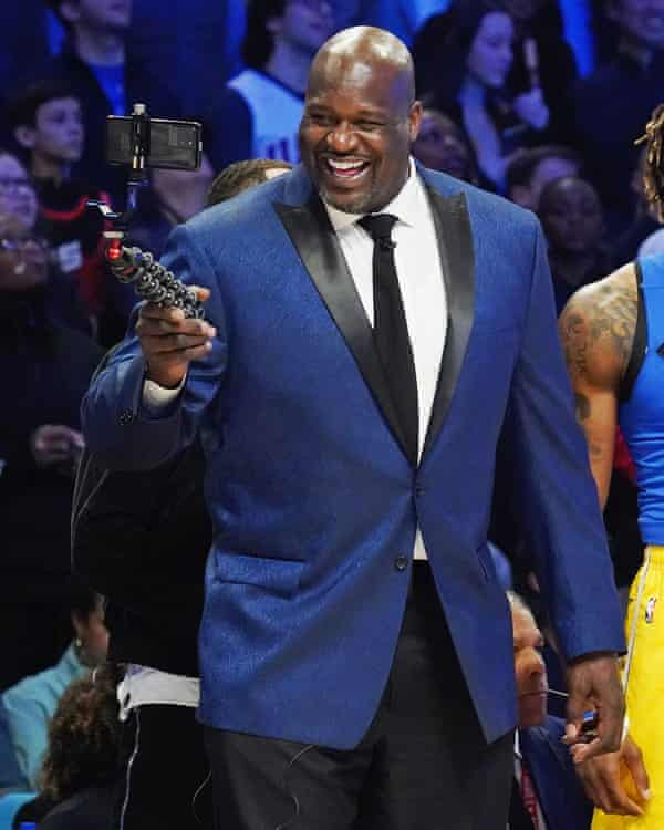 Shaquile O'Neal smiling into a phone he is holding on a selfie stick