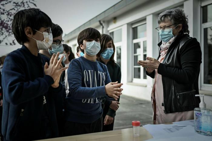 Children sanitise their hands at a school near Bordeaux, France. Researchers say the pandemic has been the biggest disruption to education in history
