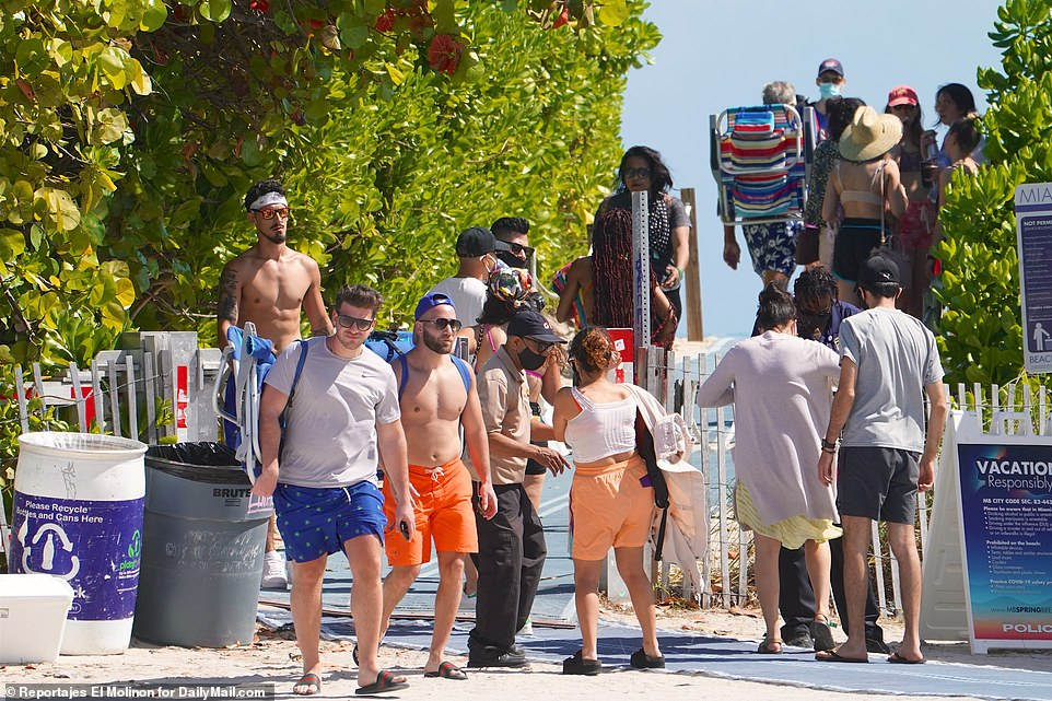 Photographs taken in Miami on Sunday show crowds of college students partying on the beach without wearing masks