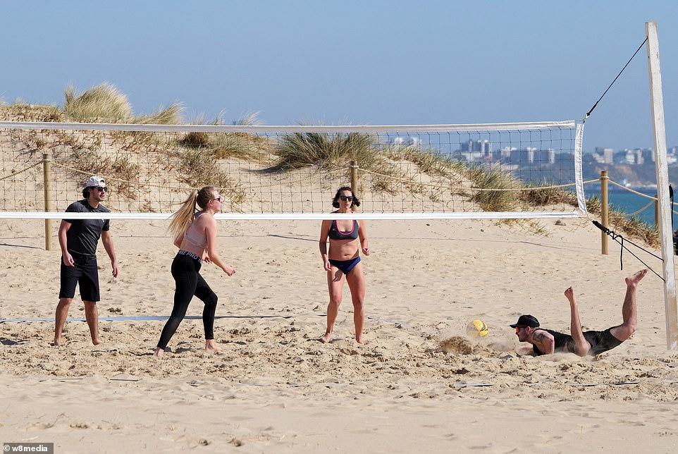 People enjoy the weather on sunny Sandbanks beach in Dorset as a group of four people play volleyball on the sand