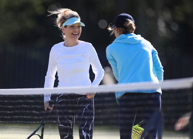 Tennis players smile during a game of doubles as members return at Grantham Tennis Club, Lincolnshire