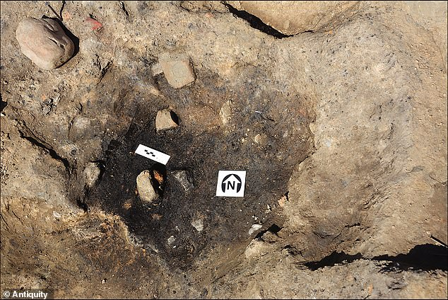 Pictured, one of the hearthes at the site showing fire-reddened stones, including one with circular marking (top, centre)