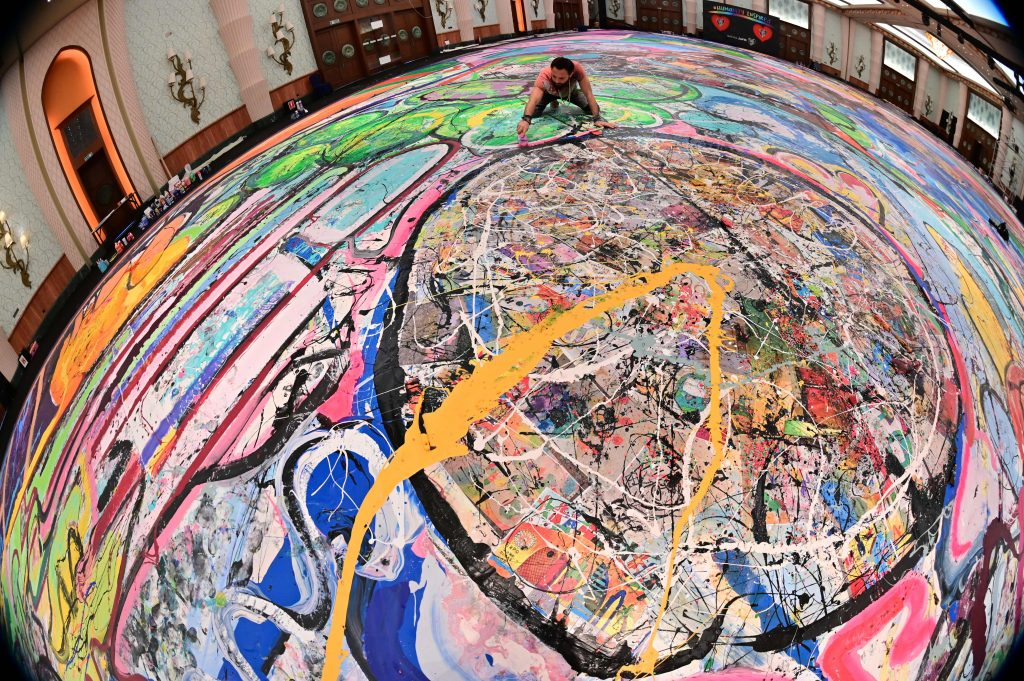 A picture taken with fisheye lens shows contemporary British artist Sacha Jafri working on his record-breaking painting entitled The Journey of Humanity on September 23, 2020, in the Emirati city of Dubai. Jafri spent months of lockdown at the Atlantic, the Palm, hotel due to the pandemic. The painting's $62 million sale will fund health and education initiatives for children living in poverty worldwide. Photo by Giuseppe Cacace/AFP via Getty Images.