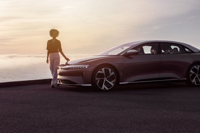 A woman walks past the Lucid Air electric car on a beach at sunset.