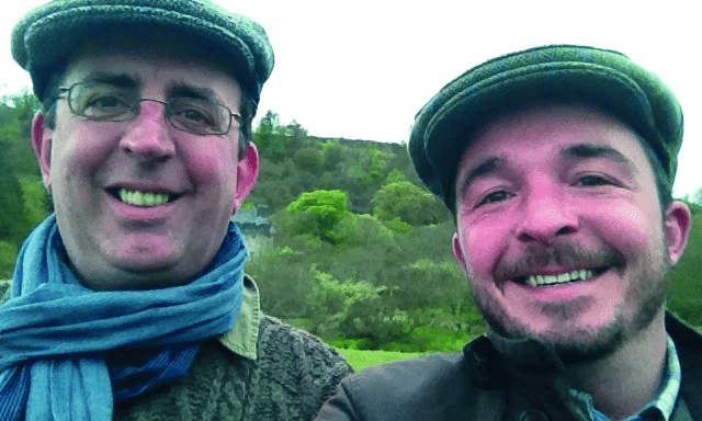 Reverend Richard Coles with husband David Oldham, both in flat caps