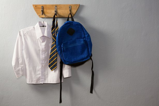 School uniform and schoolbag hanging on hook against wall