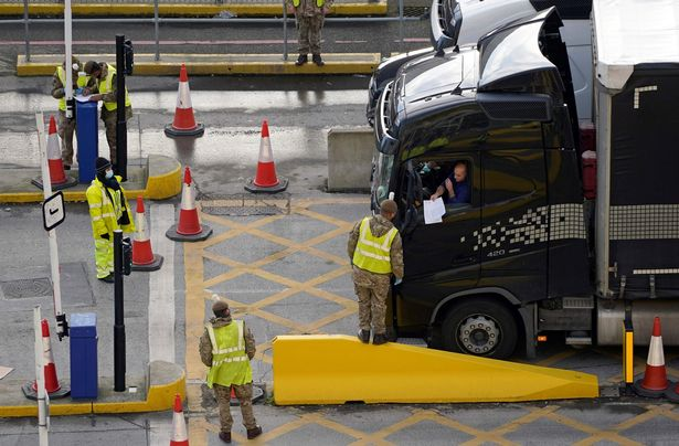A lorry driver shows their credentials to a member of the British Army, as they enter the Port of Dover
