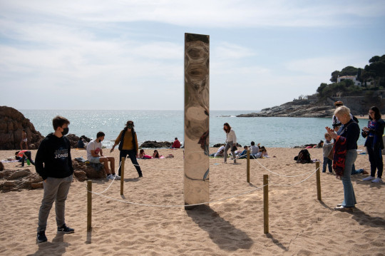 People observe and photograph on March 31, 2021 a metal monolith that has popped up on Sa Conca beach in Castell-Platja D'Aro, near Girona, the latest in a string of similar objects that have recently appeared around the world since a first similar column appeared in a desert of Utah, United States in November 2020. (Photo by Josep LAGO / AFP) (Photo by JOSEP LAGO/AFP via Getty Images)