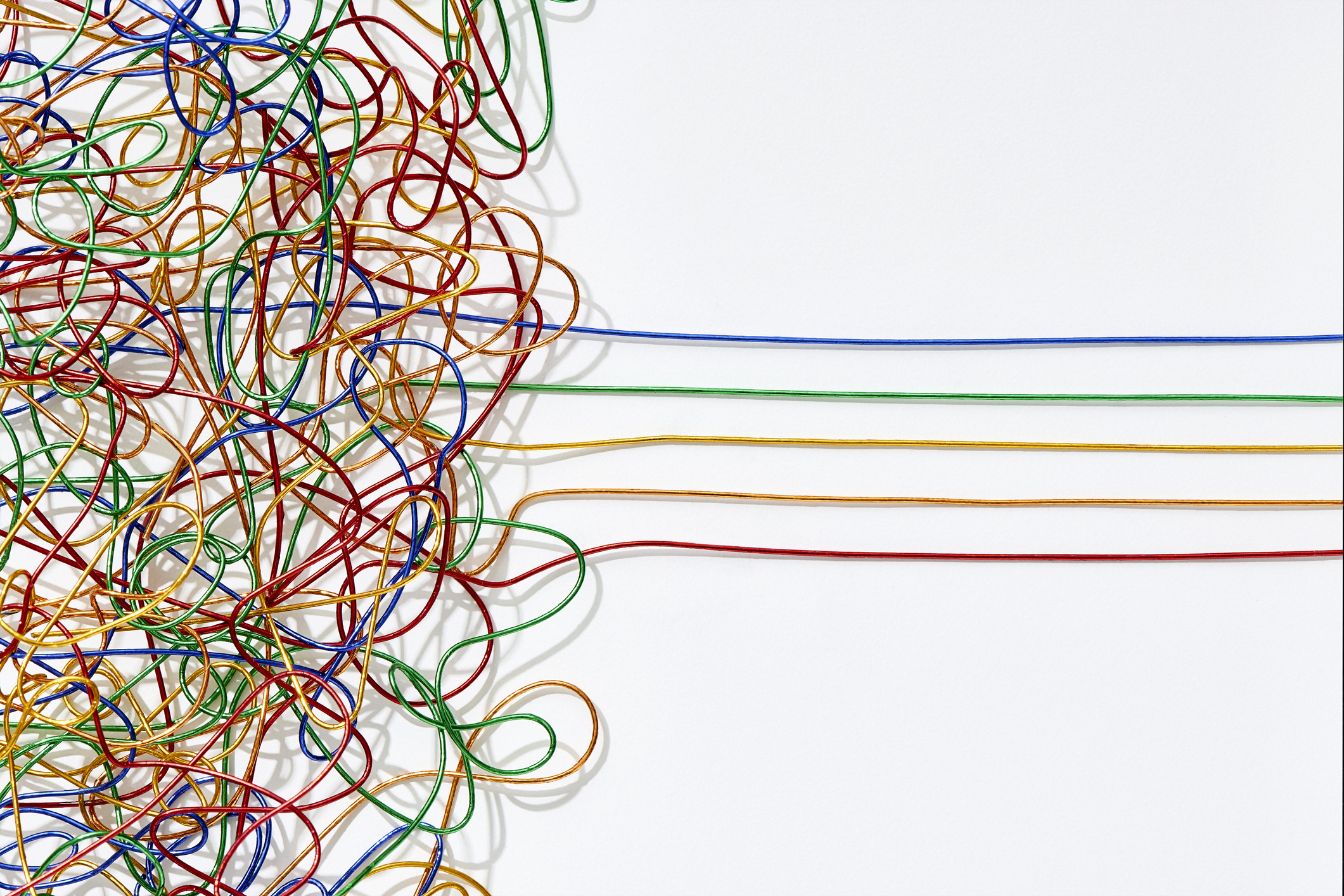 Jumble of multicoloured wires untangling into straight lines over a white background. Cape Town, South Africa. Feb 2019.