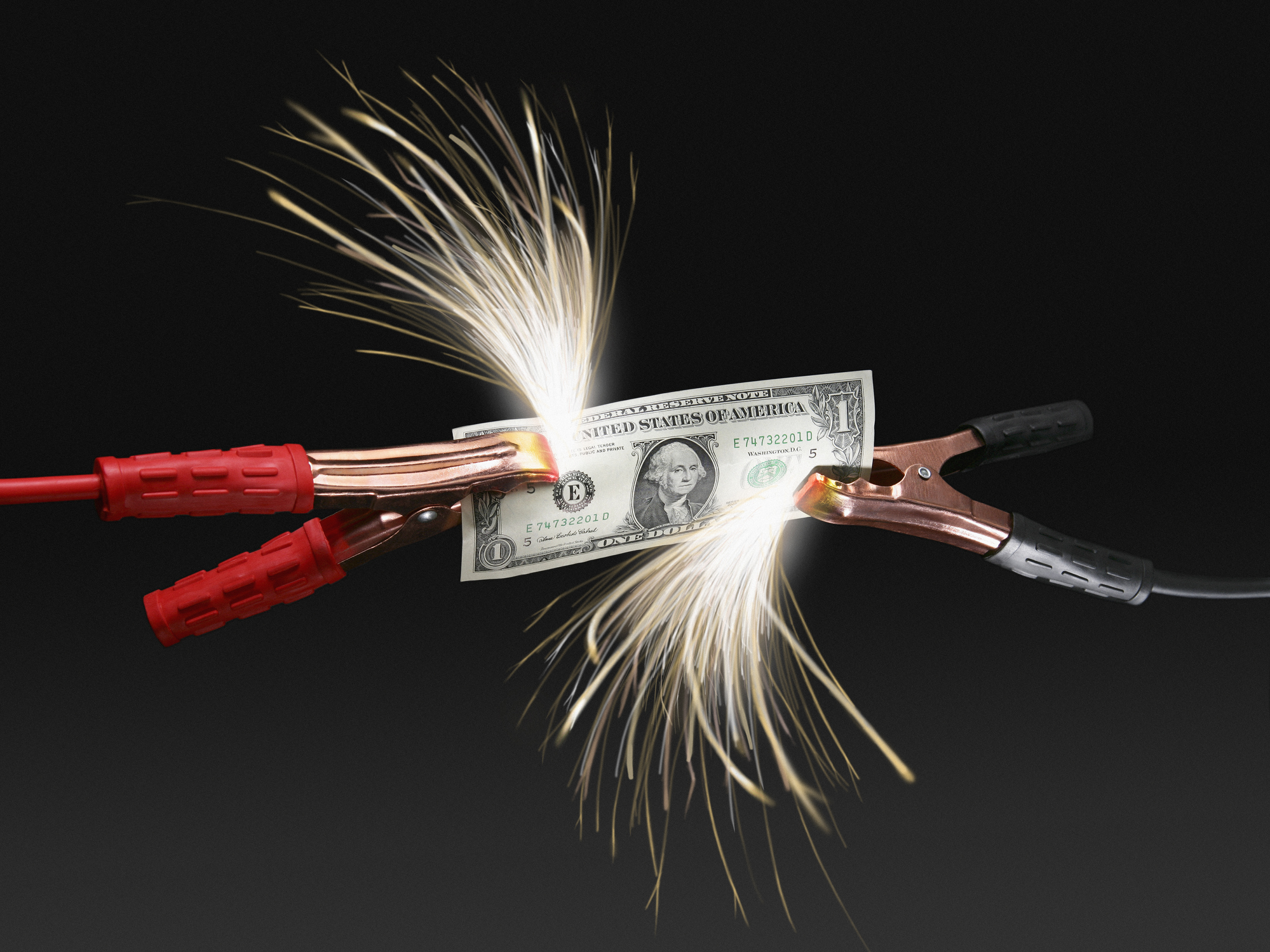 Sparks coming off US dollar bill attached to jumper cables