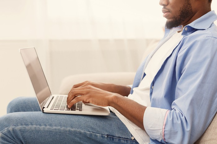 A man using a laptop while sitting.