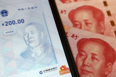 China's official app for digital yuan is seen on a mobile phone next to 100-yuan banknotes, 16 October 2020 (Photo: Reuters/Florence Lo).