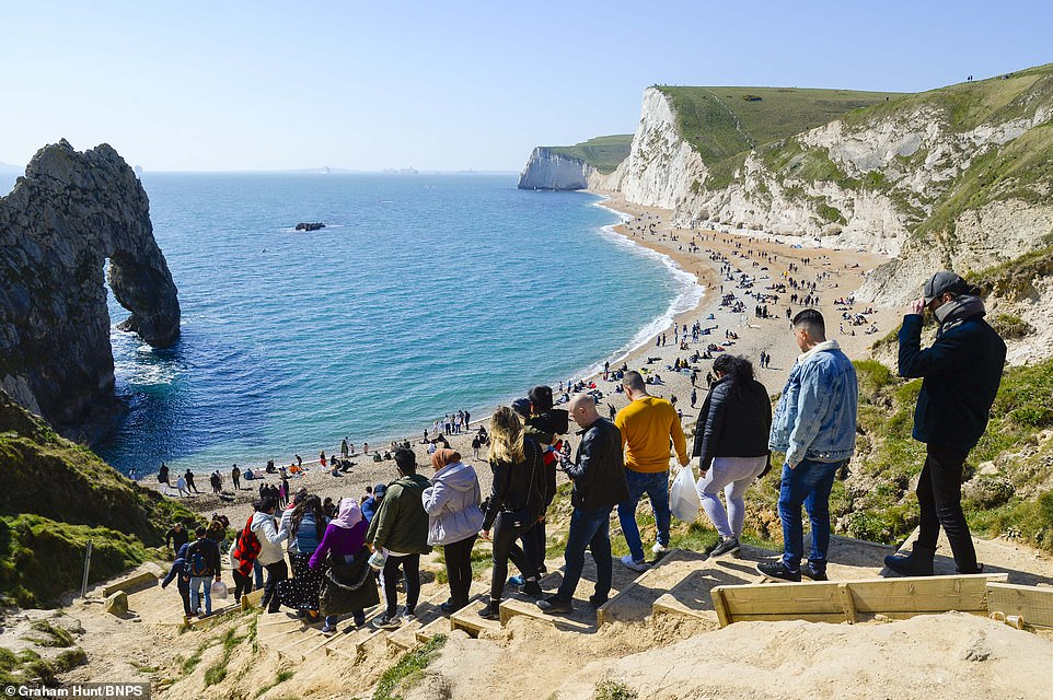 Visitors flock to Durdle Door in Dorset on a day of warm spring sunshine and a cool breeze during Easter Sunday