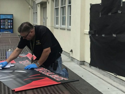 Burlingame High worker Victor Delaplaine scrubs a swastika from a school banner, Aug. 5, 2019. (Photo/The Burlingame B)