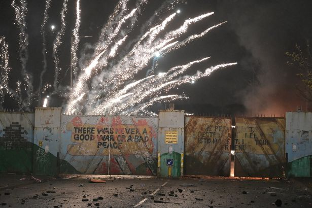 Fireworks explode as youths exchange projectiles through the Peace Gate