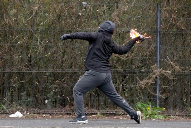 A nationalist youth throws a petrol bomb at police officers in the Springfield Road area