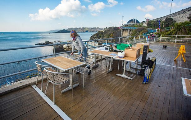 Lesleigh Mason prepares tables at The Terrace Cafe and Bar in Plymouth, Devon, ahead of the reopening on Monday