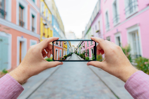 Person taking photo of street on phone