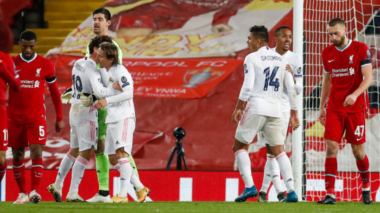 Álvaro Odriozola with Luka Modric, Carlos Casemiro and Éder Militão celebrating during the UEFA Champions League Quarter Final Second Leg match between Liverpool FC and Real Madrid at Anfield on April 14, 2021 in Liverpool, England. Sporting stadiums around the UK remain under strict restrictions due to the Coronavirus Pandemic as Government social distancing laws prohibit fans inside venues resulting in games being played behind closed doors.