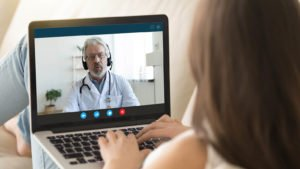 A woman talks to a doctor on her laptop. telehealth stocks