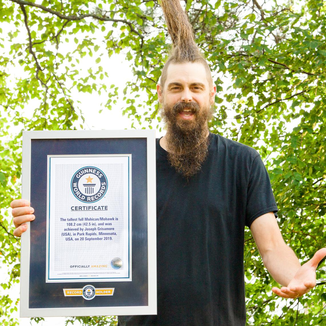 Grisamore poses with his official Guinness World Record certificate for the tallest full Mohican mohawk, which he accomplished in September 2019.