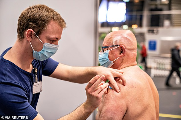 Pictured: A medical worker vaccinates a man against the coronavirus disease (COVID-19) in Frederikshavn, Jutland, Denmark, April 12, 2021 - two days before the country ceased to administer the AstraZeneca vaccine over blood clot fears