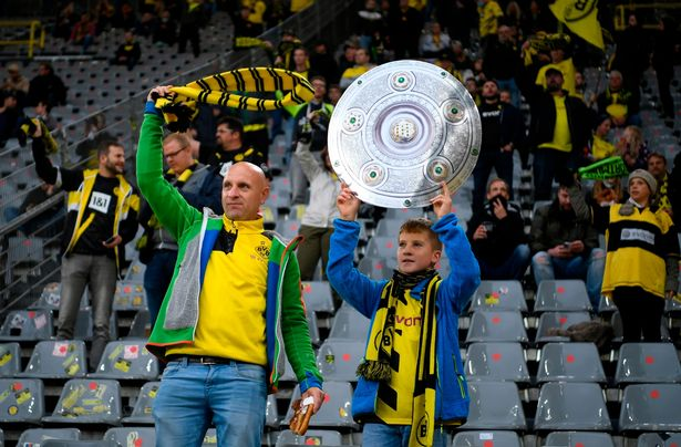 Supporters celebrate their team with a mock-up of the German Championship trophy before the German first division Bundesliga football match Borussia Dortmund v SC Freiburg in Dortmund, western Germany, on October 3, 2020.