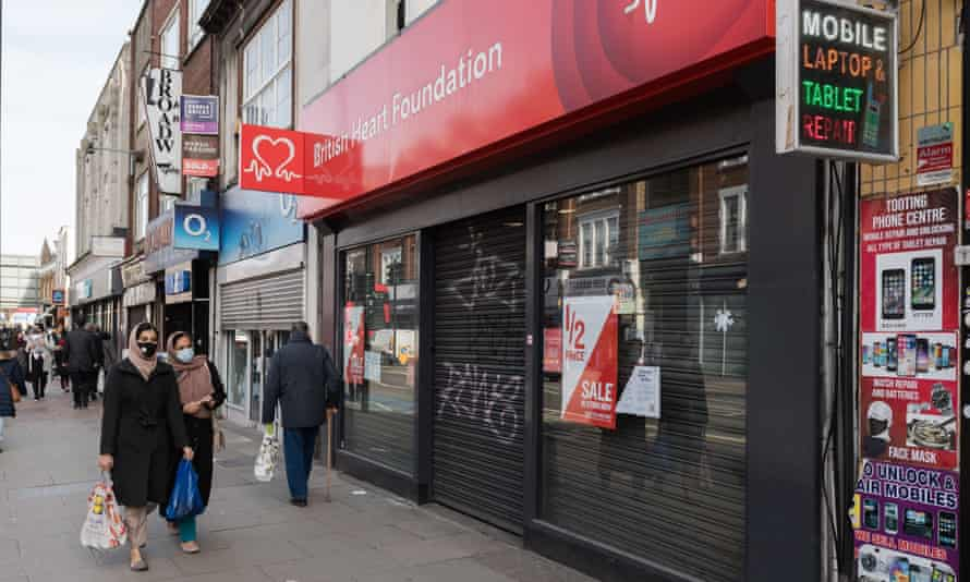 A BHF shop with its security shutters down and people in masks walking past