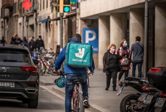 A rider from the deliveroo company rides along the Ramblas