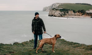 Daniel Payne stands with his dog Drago on the coastal path overlooking Freshwater Bay