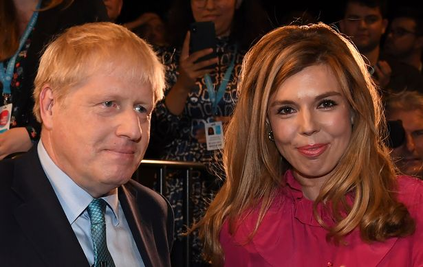 Britain's Prime Minister Boris Johnson leaves with his partner Carrie Symonds after delivering his keynote speech to delegates on the final day of the annual Conservative Party conference at the Manchester Central convention complex, in Manchester, north-west England on October 2, 2019.
